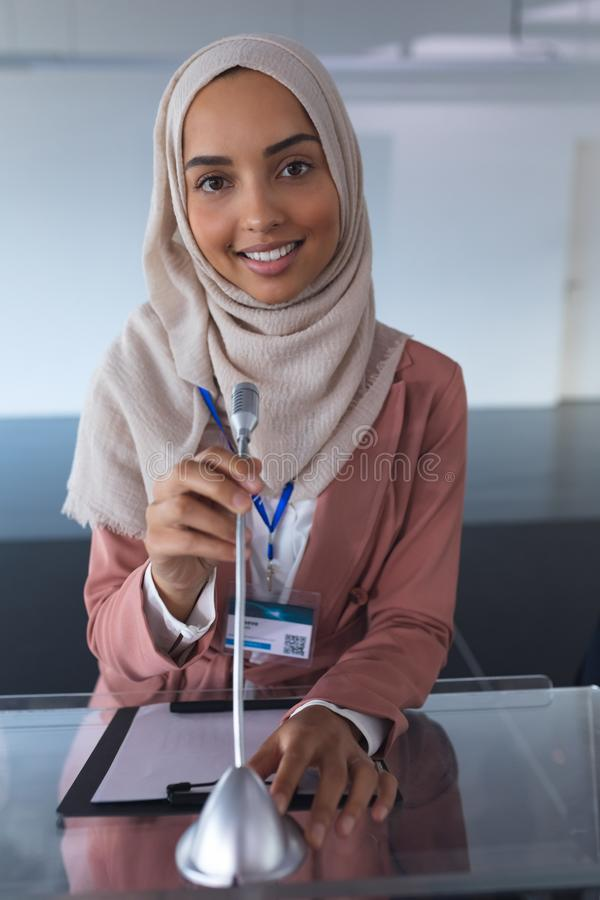 Żeński mówca patrzeje kamerę w hijab podczas gdy mówjący w biznesowym konwersatorium zdjęcia royalty free