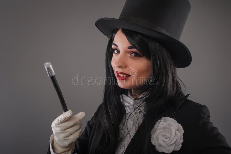 Żeński magik w kostiumowym kostiumu z magicznym kijem robi sztuczce obraz stock