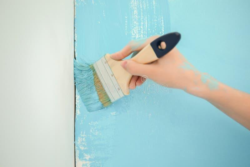 Żeński malarz używa muśnięcie dla odczyszczać kolor ściana indoors obrazy stock