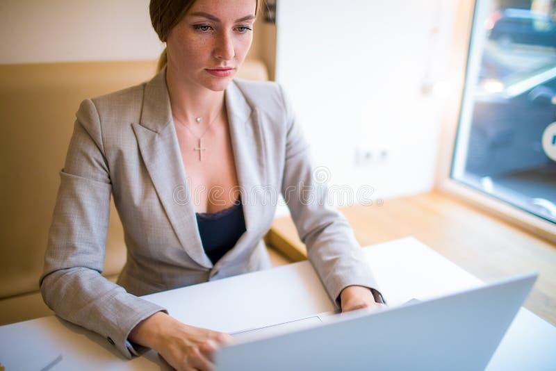 Żeński marketingowy pisarski działanie na nowożytnym netbook przyrządzie, odpoczywa w sklepie z kawą obraz royalty free