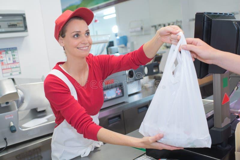 Żeński masarki porci klient na sklepie spożywczym zdjęcia stock
