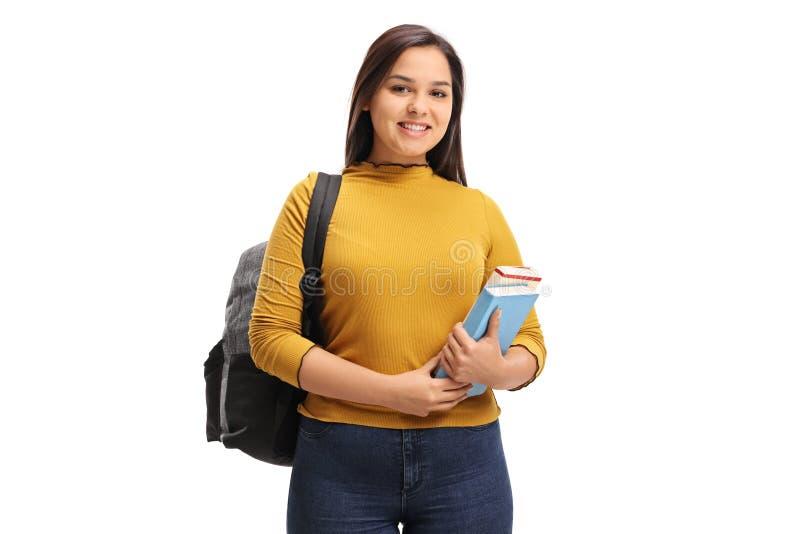 Żeński nastoletni uczeń z plecaka i książek ono uśmiecha się obrazy stock