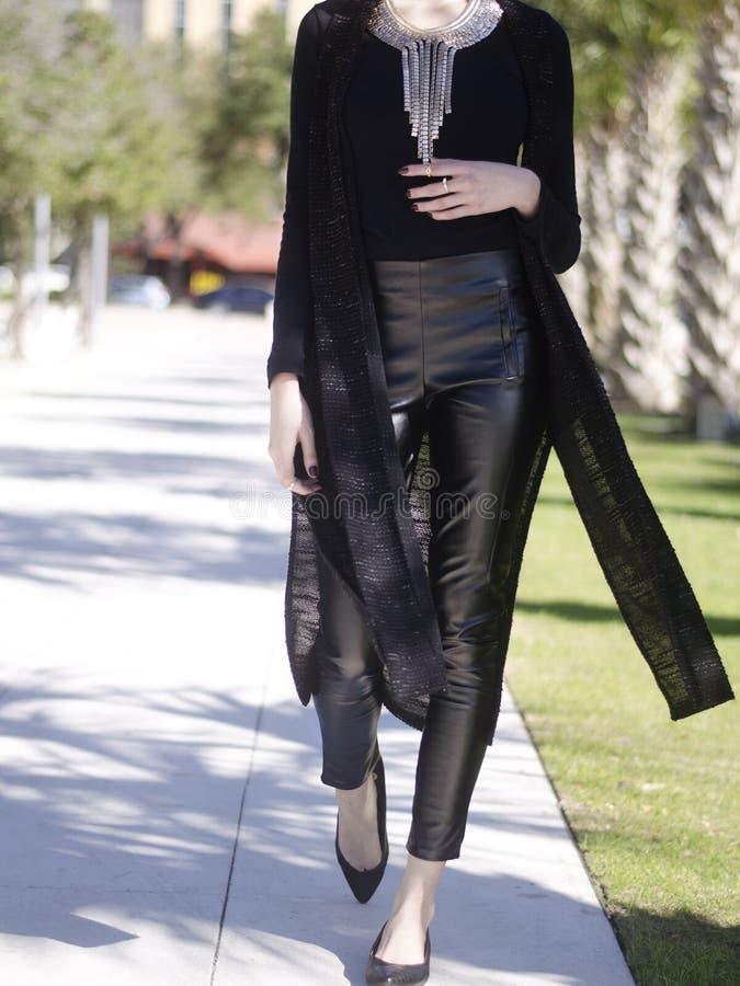 Żeński odprowadzenie jest ubranym czarnych skór spodnia, czarną bluzkę, długą kurtkę i złoto kolię, obraz stock