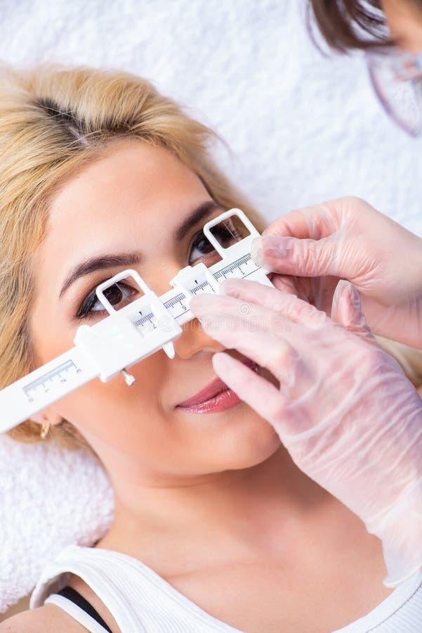 Żeński oftalmolog sprawdza w górę żeńskiego pacjenta w oka doct obrazy stock