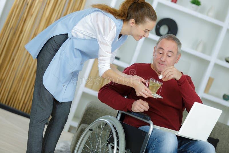Żeński opiekun daje medycynie starszy mężczyzna w domu obrazy royalty free