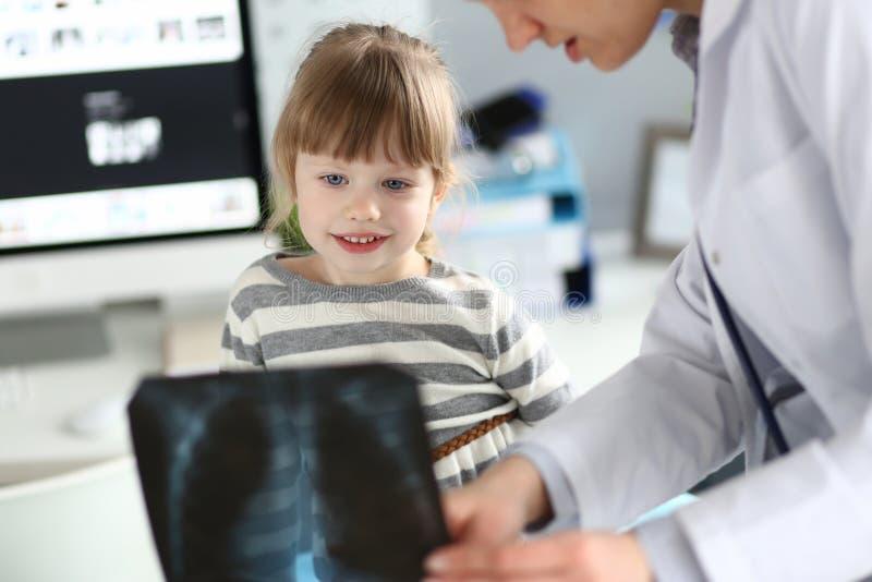 Żeński paediatrician pracuje z śliczną małą dziewczynką przy jej biurową wyjaśnia diagnozą obraz royalty free