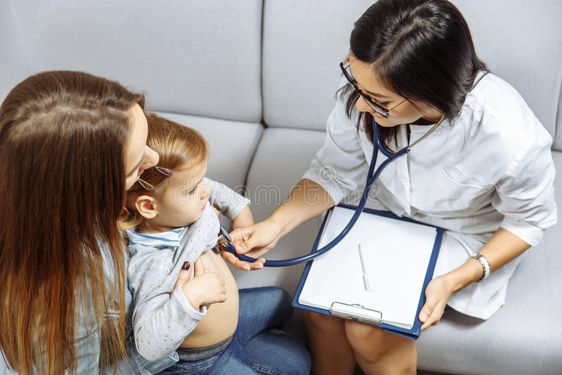 Żeński pediatra egzamininuje małej dziewczynki z stetoskopem Macierzysty mienie jej dzieciak Doktorska wizyta jego pacjent w domu obraz stock