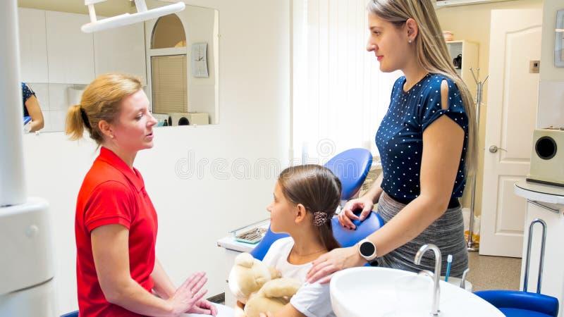 Żeński pediatryczny dentysta opowiada dziewczyna i jej matka w dentysty biurze fotografia stock