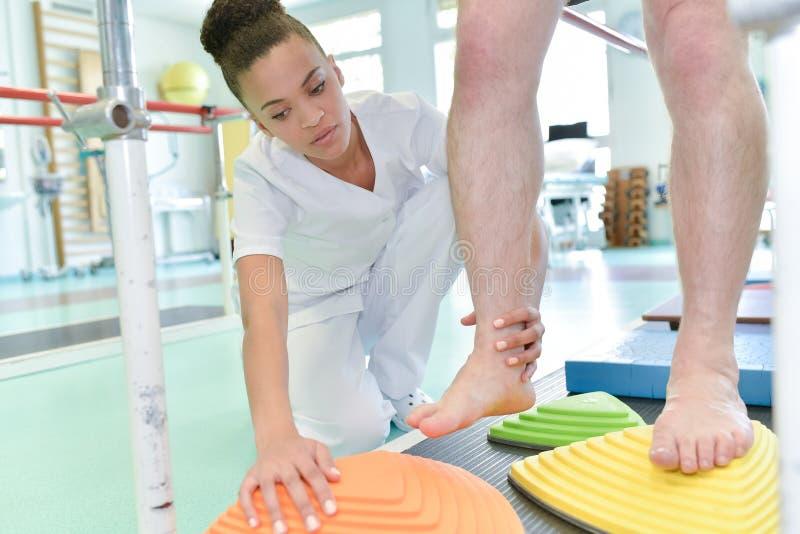 Żeński physiotherapist daje poparciu męski pacjent w klinice zdjęcia stock