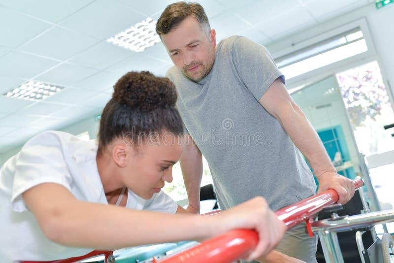Żeński physiotherapist pomaga męskiego pacjenta chodzić obraz royalty free
