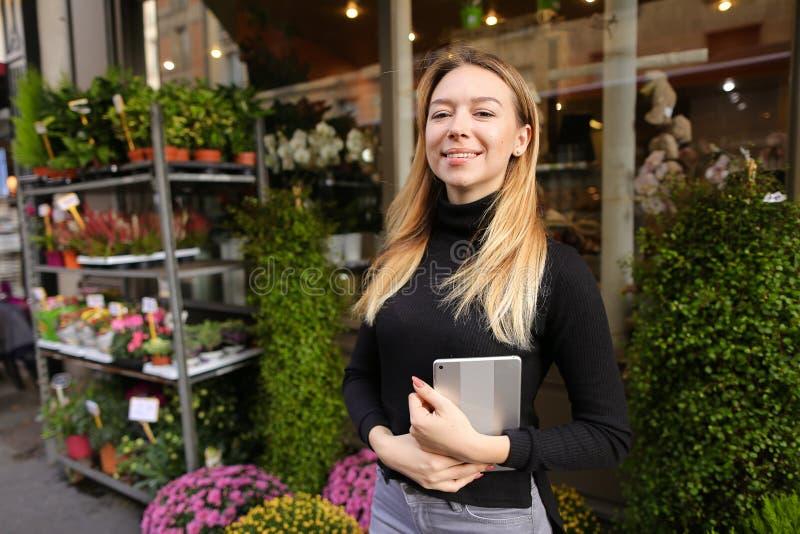 Żeński piękny kierownik kwiatu sklepu pozycja z pastylką blisko izbowych rośliien obrazy stock