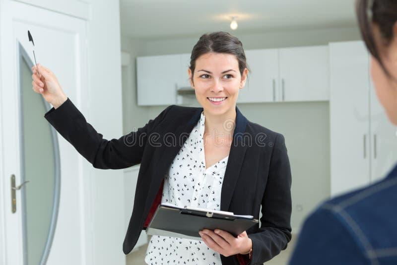 Żeński pośrednik w handlu nieruchomościami pokazuje mieszkanie zdjęcie royalty free