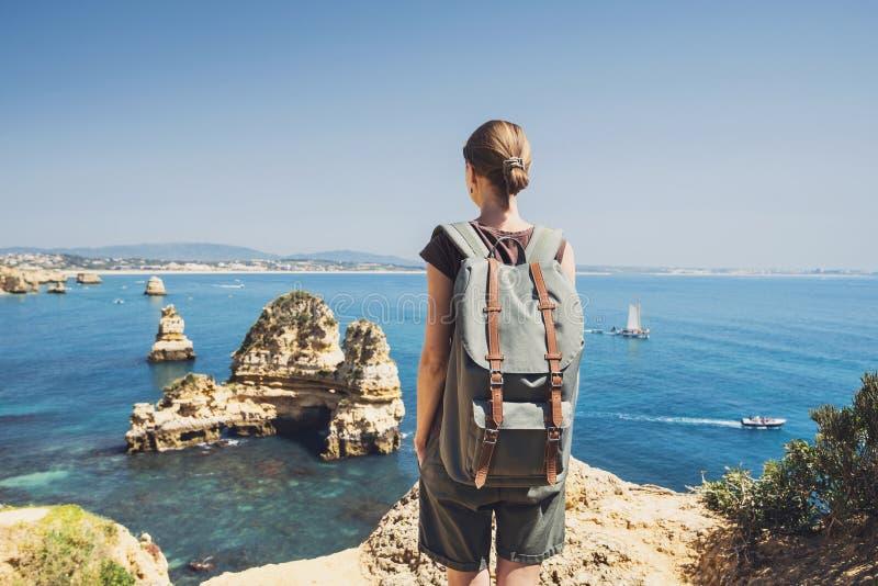 Żeński podróżnik patrzeje morze w Lagos miasteczku, Algarve region, Portugalia podróży i aktywnego stylu życia pojęcie obraz stock
