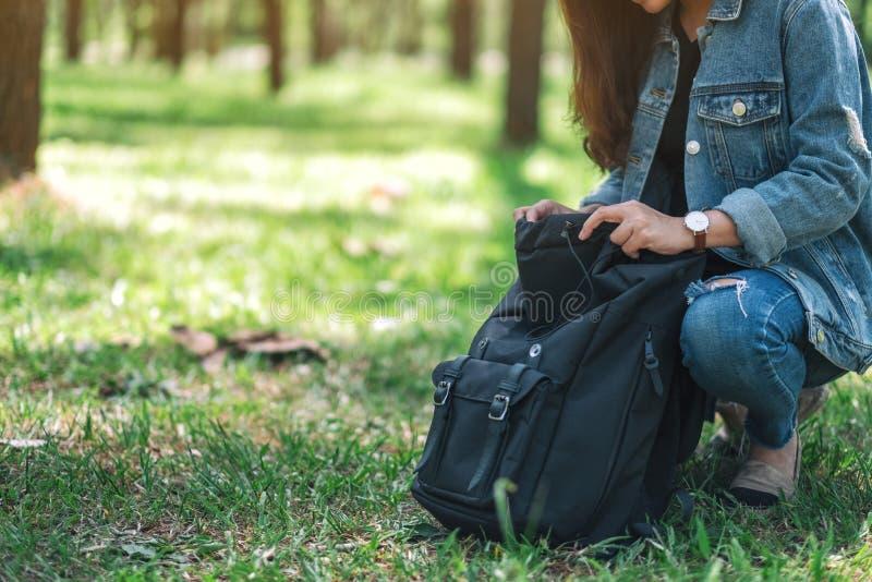 Żeński podróżnik z kapeluszowym otwarciem jej plecak podczas gdy podróżujący w pięknych sosnowych drewna obrazy stock