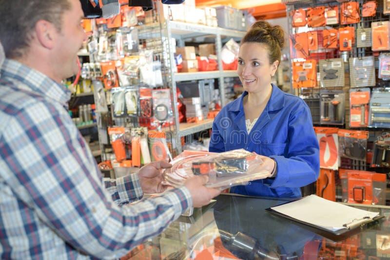 Żeński pracownik rozdaje z klientem w magazynowym sklepie obraz royalty free