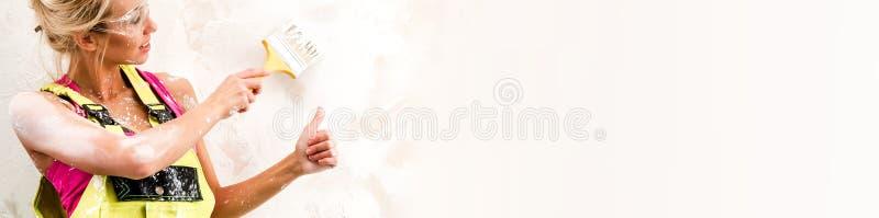 Żeński pracownik w coverall farby ściennych pokazuje aprobatach panoramiczny wizerunek zdjęcie stock