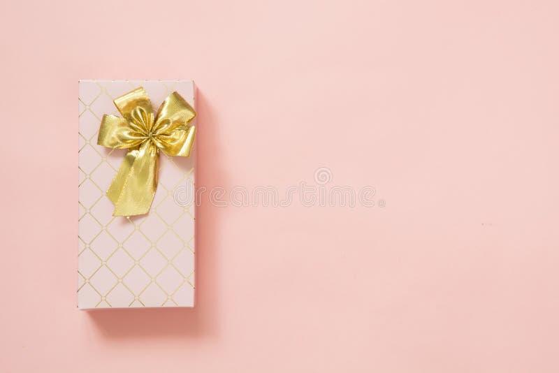 Żeński prezenta pudełko z złotym faborkiem na punchy pastelowych menchiach Urodziny kosmos kopii obrazy stock