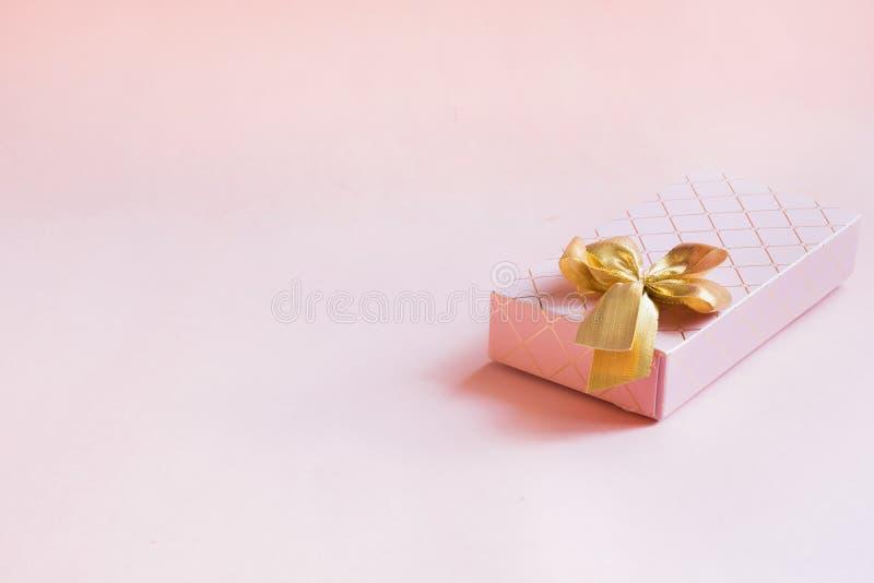 Żeński prezenta pudełko z złotym faborkiem na punchy pastelowych menchiach Urodziny kosmos kopii fotografia stock