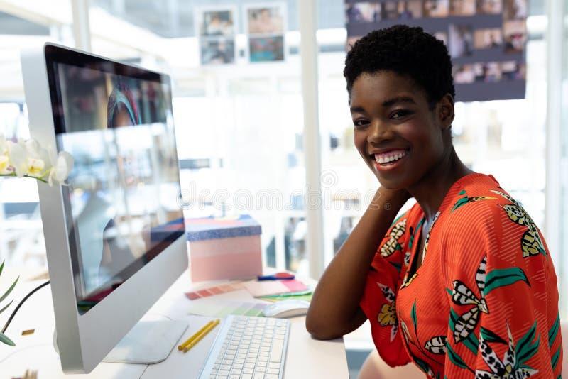 Żeński projektant grafik komputerowych ono uśmiecha się przy biurkiem w biurze zdjęcia royalty free