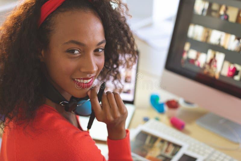 Żeński projektant grafik komputerowych patrzeje kamerę podczas gdy siedzący przy biurkiem zdjęcie royalty free