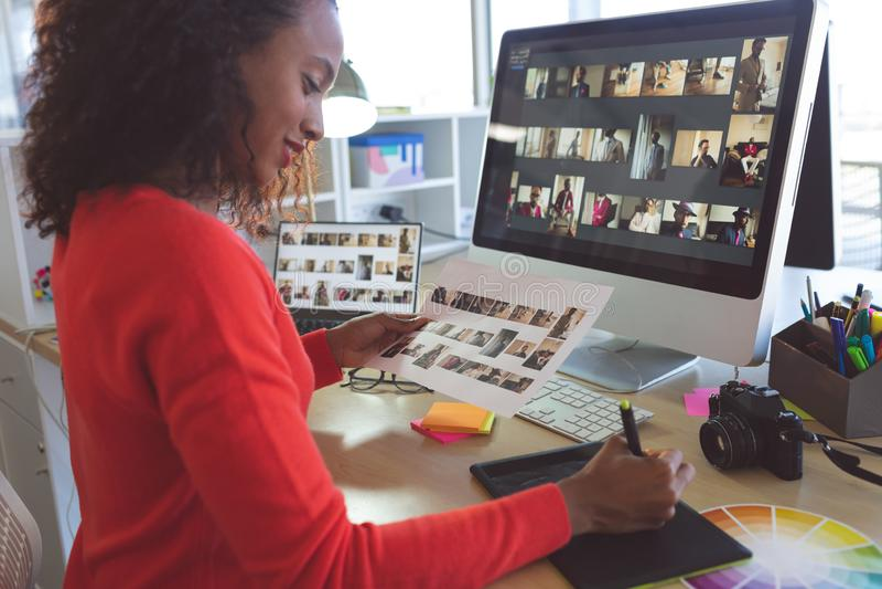 Żeński projektant grafik komputerowych pisze przy biurkiem zdjęcie royalty free