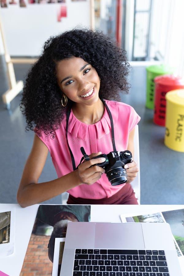 Żeński projektant grafik komputerowych przegląda fotografie na cyfrowej kamerze przy biurkiem w biurze zdjęcie stock