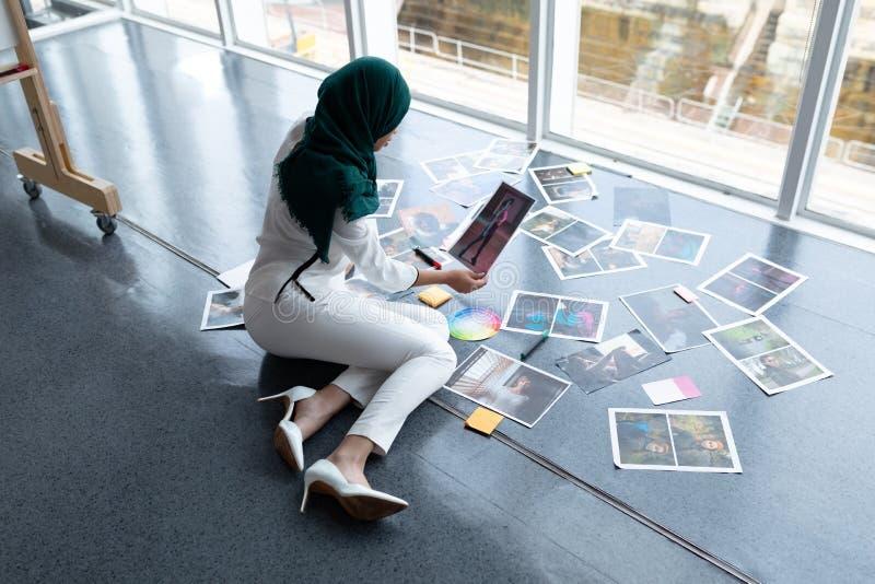 Żeński projektant grafik komputerowych sprawdza fotografie w biurze w hijab fotografia stock