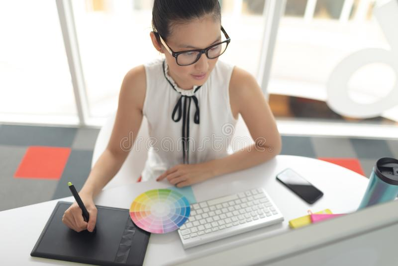 Żeński projektant grafik komputerowych używa graficzną pastylkę przy biurkiem w nowożytnym biurze obraz stock