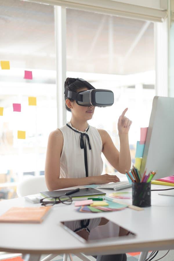 Żeński projektant grafik komputerowych używa rzeczywistości wirtualnej słuchawki przy biurkiem w nowożytnym biurze fotografia stock