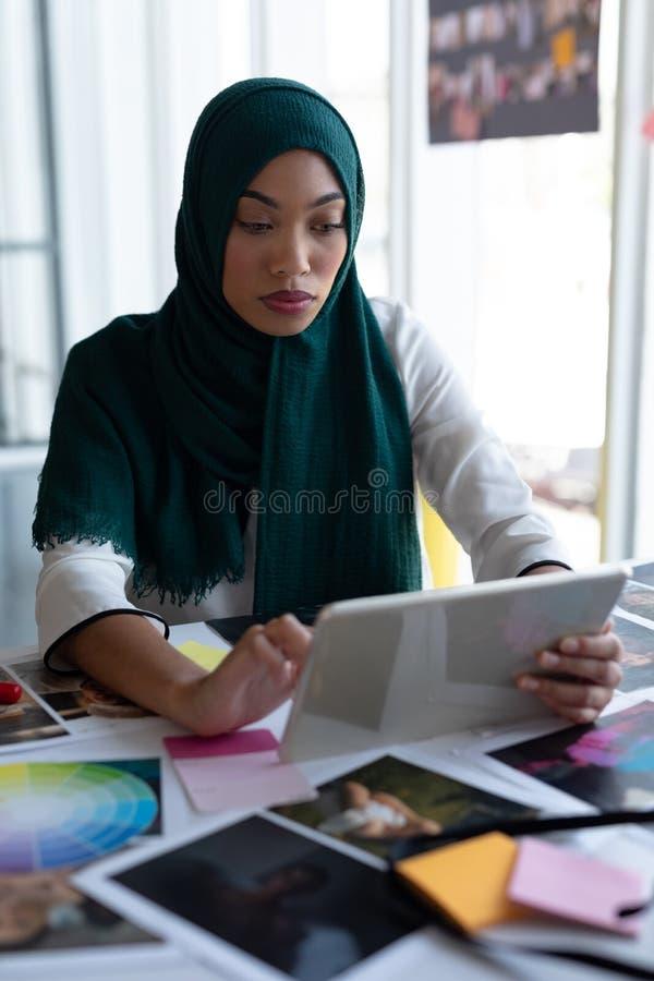 Żeński projektant grafik komputerowych w hijab używać cyfrową pastylkę przy biurkiem obraz royalty free