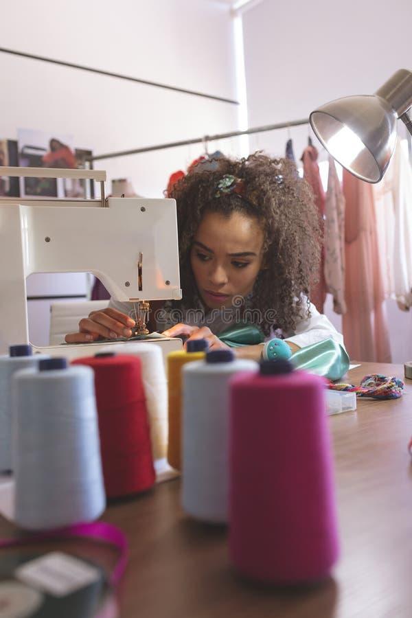 Żeński projektant mody pracuje z szwalną maszyną obrazy stock