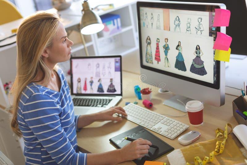 Żeński projektant mody używa graficzną pastylkę przy biurkiem podczas gdy pracujący zdjęcia stock