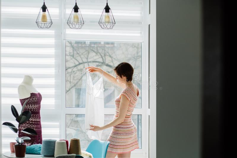 Żeński projektant pracuje z trykotową suknią w wygodnym pracownianym wnętrzu, freelance, styl życia, inspiracji pojęcie obrazy stock