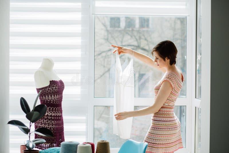 Żeński projektant pracuje z trykotową suknią w wygodnym pracownianym wnętrzu, freelance, styl życia, inspiracji pojęcie zdjęcia royalty free