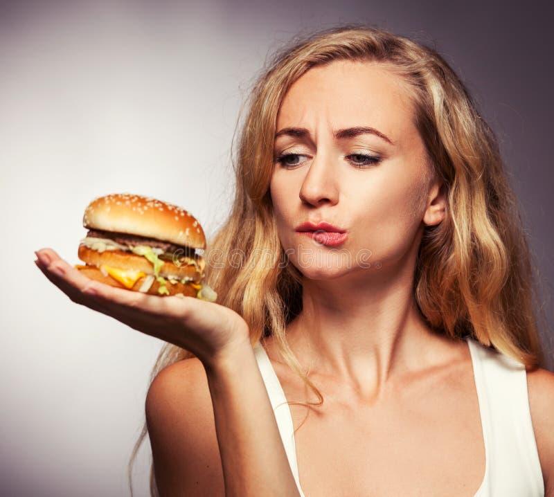 Żeński przyglądający hamburger obrazy royalty free