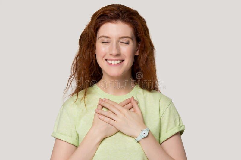 Żeński przymknięcie ona oko chwytów ręki na klatce piersiowej czuje wdzięczność zdjęcia stock