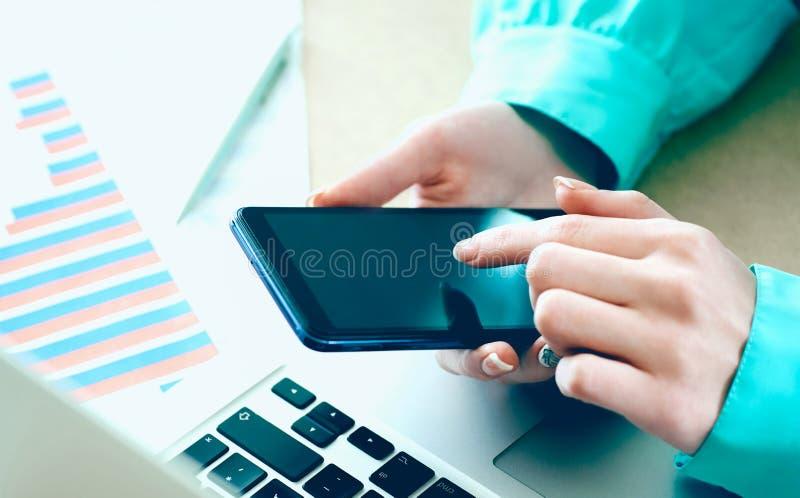 Żeński ręka chwytów smartphone wskazuje palcowego ekranu sensorowego telefon, laptopów pieniężni wykresy na tle zdjęcia stock