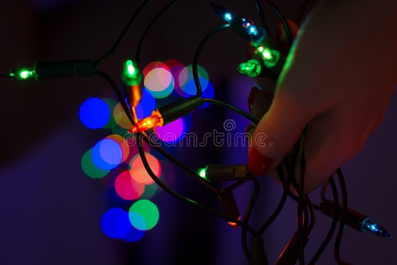 Żeński ręki mienia sznurek bożonarodzeniowe światła z defocused xmas drzewem w tle Bożonarodzeniowe światła bokeh obrazy royalty free