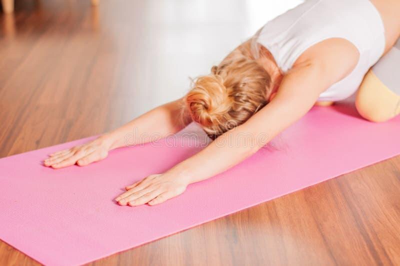 Żeński robi rozciąganie na sprawności fizycznej macie Kobieta robi balasana joga w domu zdjęcia stock