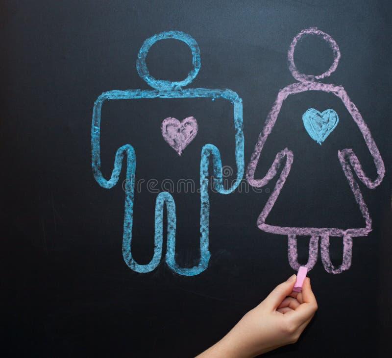Żeński rodzaju symbol jest równy męski pojęcie równouprawnienie płci Rysować z kredą na kredowej desce fotografia stock