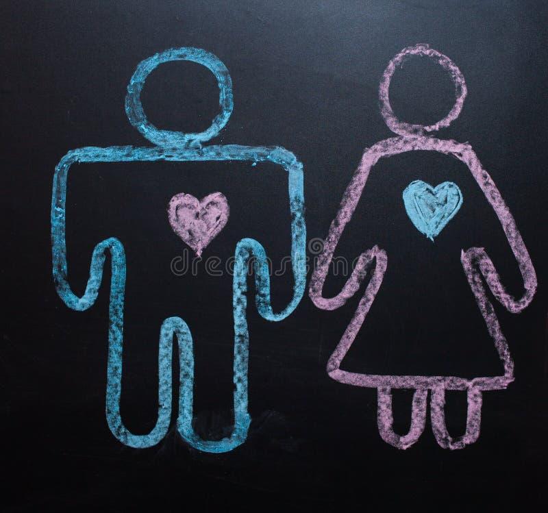 Żeński rodzaju symbol jest równy męski pojęcie równouprawnienie płci Rysować z kredą na kredowej desce obraz stock