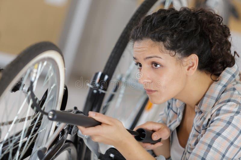 Żeński roweru technik pompuje w górę roweru zdjęcia stock