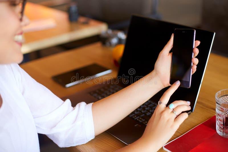 Żeński skanerowanie odcisk palca na jej smartphone z laptopem na backround Kobieta otwiera telefon komórkowego z biometrycznym cz fotografia royalty free