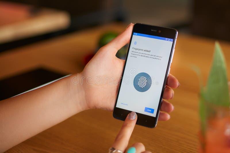 Żeński skanerowanie odcisk palca na jej smartphone z programa pismem na laptopu pokazie na backround Kobieta otwiera wiszącą ozdo obrazy stock