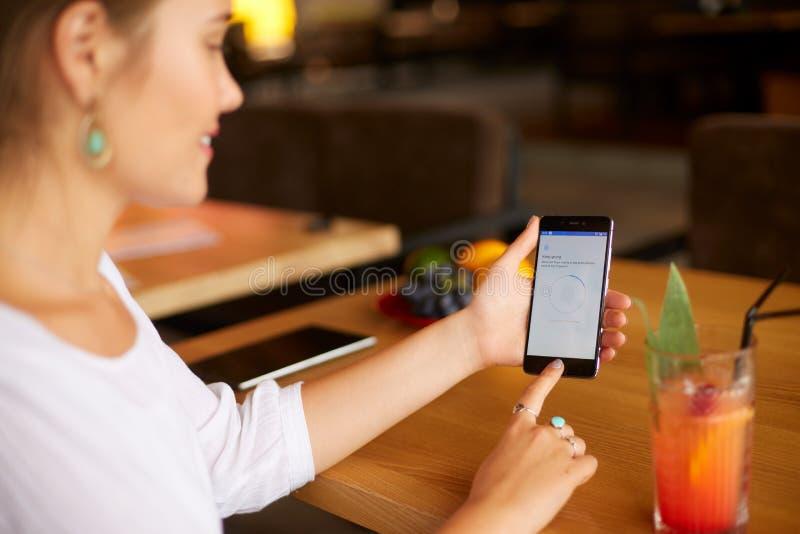 Żeński skanerowanie odcisk palca na jej smartphone z programa pismem na laptopu pokazie na backround Kobieta otwiera wiszącą ozdo zdjęcia royalty free