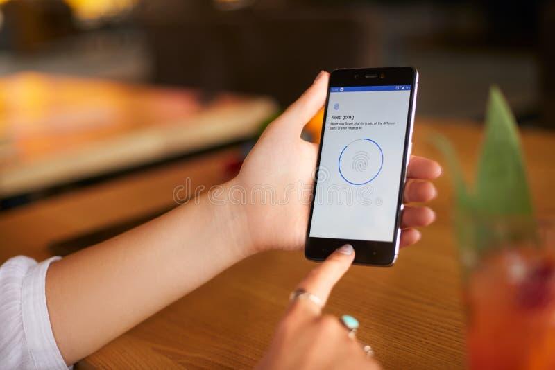 Żeński skanerowanie odcisk palca na jej smartphone z programa pismem na laptopu pokazie na backround Kobieta otwiera wiszącą ozdo zdjęcie stock