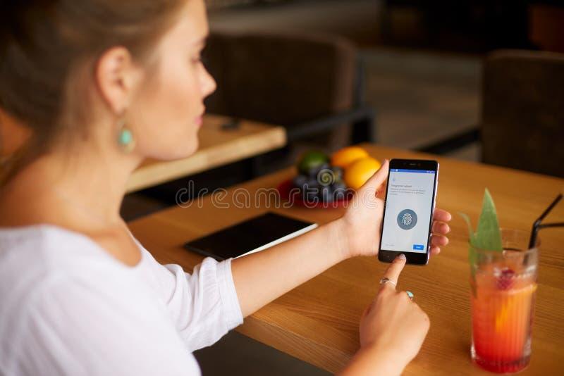 Żeński skanerowanie odcisk palca na jej smartphone z programa pismem na laptopu pokazie na backround Kobieta otwiera wiszącą ozdo zdjęcie royalty free