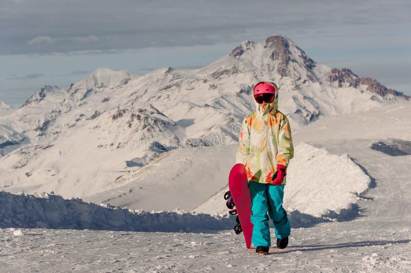 Żeński snowboarder w sportswear odprowadzeniu na tle halni szczyty fotografia stock
