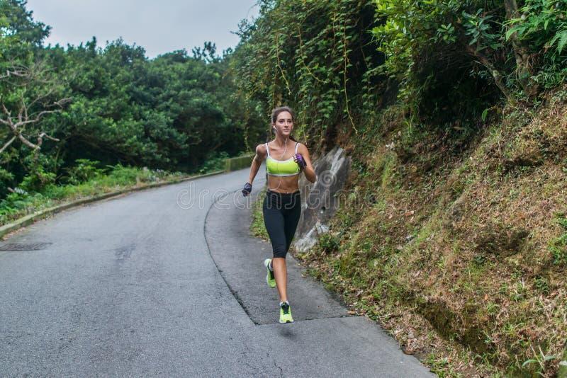 Żeński sporta modela bieg na drodze w górach Sprawności fizycznej kobieta trenuje outdoors obraz royalty free