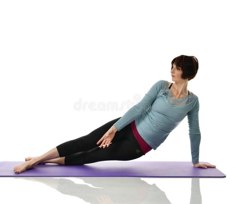 Żeński sprawność fizyczna instruktor robi rozciąganiu dla ręk nóg abdominals baru ćwiczenia w gym opracowywał odosobnionego na bi zdjęcia stock